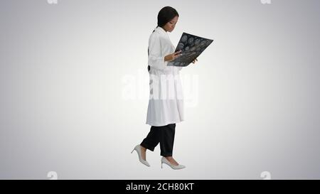 Young african american female doctor looking at xray while walki