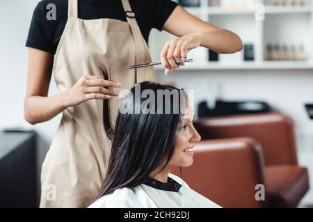 Close up portrait of happy woman getting cut of split ends at hairdresser's