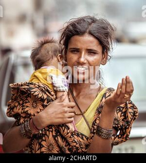 New Delhi, India - August 14, 2016: Young indian beggar woman with baby begs the alms in New Delhi, India Stock Photo