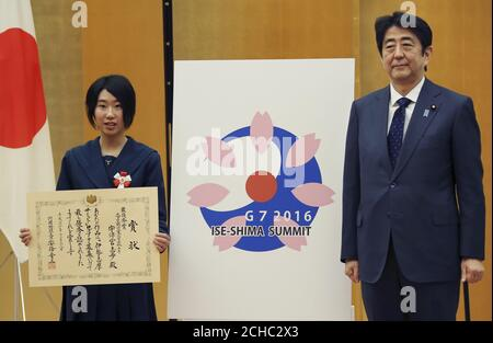 Japanese Prime Minister Shinzo Abe (R) and high school student Shiho Utsumiya pose with her design for the logo of the Ise-Shima G7 summit at the prime minister's official residence in Tokyo, Japan, December 28, 2015. REUTERS/Koji Sasahara/Pool - Stock Photo