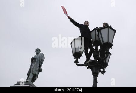 Supporters of Russian opposition leader Alexei Navalny are seen on a lamp post next to a monument of Russian poet Alexander Pushkin during a rally for a boycott of a March 18 presidential election in Moscow, Russia January 28, 2018. The placard reads 'Strike'. REUTERS/Tatyana Makeyeva - Stock Photo