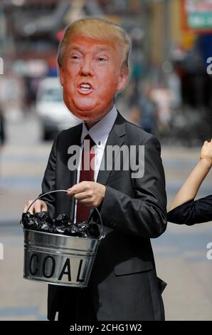 A protester wearing the mask of U.S. President Donal Trump and carrying a bucket of coal demonstrates during the G20 Summit in Osaka, Japan, June 28, 2019. REUTERS/Jorge Silva - Stock Photo