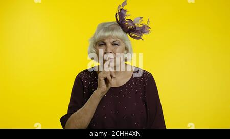 I won't tell. Senior old blond woman covering mouth promising to keep terrible secret, silence. Elderly stylish lady grandma on yellow background - Stock Photo