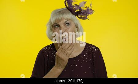 Shocked frightened senior old woman covering mouth with hand and looking terrified at camera, scared to tell truth, intimidated bullied victim. Elderly stylish lady grandma in studio - Stock Photo