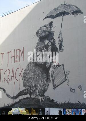 A large mural of a rat wearing a tie and carrying a briefcase on a wall on Howard St and Broadway in New York City, it is though to be the elusive British street artist Banksy's latest work in New York. - Stock Photo