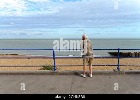 A rear view of an elderly gentleman using a mobile phone on Eastbourne seafront with the sea in the background, East Sussex England UK - Stock Photo