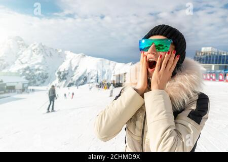 Portrait of beautiful young adult caucasian woman in sport suit, hat, sunglasses smiling looking aside and making excited amazed face expression on - Stock Photo