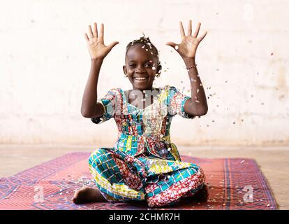 African Fun Party Girl, smiling woman throwing confetti, against a White background with Copy Space