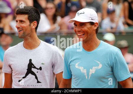 Tennis - French Open - Roland Garros, Paris, France - May 26, 2018. Spain's Rafael Nadal and Serbia's Novak Djokovic react during an exhibition match.  REUTERS/Pascal Rossignol - Stock Photo