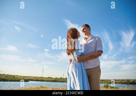 A young couple hugs in a field against the background of a river or lake and enjoy life. The concept of love and correct non-abusive relationships.