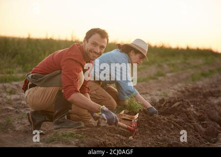 Full length portrait of two people working in field at vegetable plantation, focus on young man planting saplings in foreground and smiling at camera, copy space Stock Photo