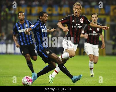 AC Milan's Keisuke Honda (R) challenges Inter Milan's Fredy Guarin (L) during the Italian Serie A soccer match at the San Siro stadium in Milan, Italy, September 13, 2015. REUTERS/Giorgio Perottino - Stock Photo