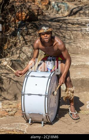 Zulu man in traditional dress playing the drum - Stock Photo