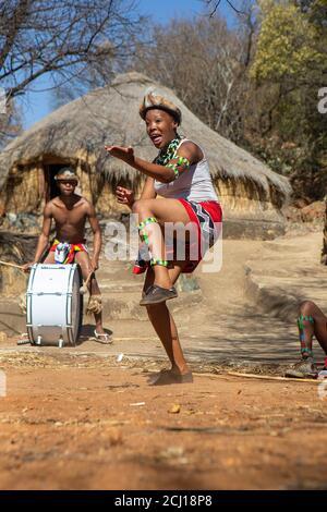 Zulu dancers in traditional costume, dancing the Ingoma warrior dance. Creda Mutwa village, South Africa - Stock Photo