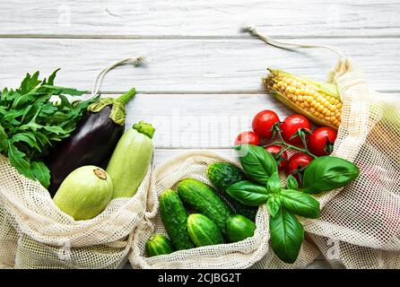 Fresh vegetables in eco cotton bags on table in the kitchen.  Fresh vegetables from market. Zero waste shopping concept.