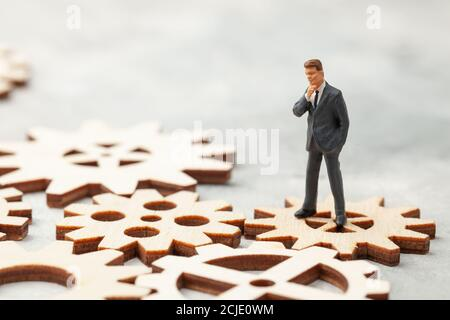 Business Analysis. Audit of the company. A businessman in a suit stands on gears as a symbol of business processes in the company.