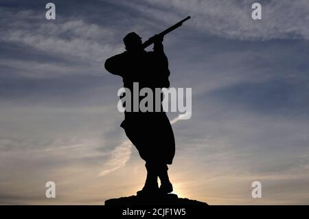 Bronze statue of a French infantryman or poilu silhouetted against the rising sun on the town monument at Monpazier in the Dordogne, Nouvelle-Aquitaine, France, to those who fell in the Franco-Prussian War of 1870-71.