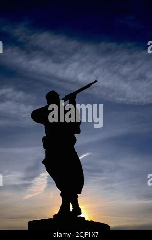 Bronze statue of a French rifleman or poilu silhouetted against the rising sun on the town monument at Monpazier in the Dordogne, Nouvelle-Aquitaine, France, to those who fell in the Franco-Prussian War of 1870-71.