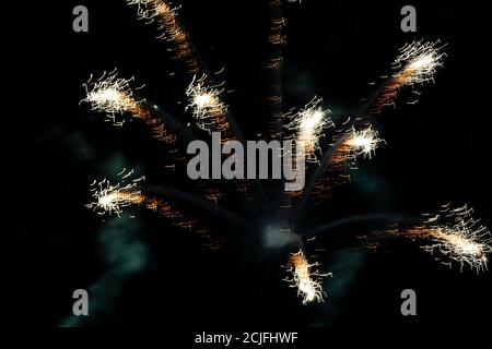 Bright light spots of fireworks of golden color on a black background. - Stock Photo