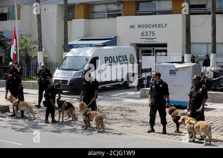 Police officers with dogs stand guard outside the hospital, after the announcement that Peru's former President Alan Garcia died in the hospital after shooting himself, in Lima, Peru April 17, 2019. REUTERS/Guadalupe Pardo