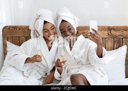 Stunning girlfriends in bathrobes sitting on bed and taking selfie
