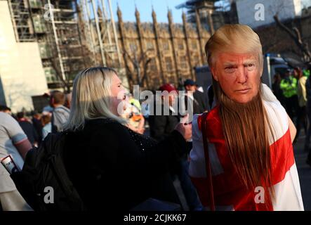 A pro-Brexit protester wearing a mask depicting U.S. President Donald Trump, is seen outside the Houses of Parliament in London, Britain March 29, 2019. REUTERS/Hannah Mckay - Stock Photo