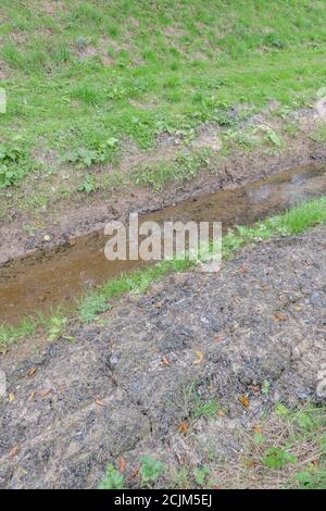 Free-flowing agricultural field drain recently cleaned and cleared of aquatic weeds. For land management, water run-off management, flood control. - Stock Photo