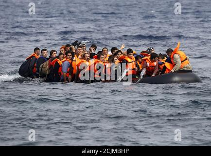 Syrian refugees call for help and empty water from their flooding raft as they approach  the Greek island of Lesbos October 20, 2015.Thousands of refugees - mostly fleeing war-torn Syria, Afghanistan and Iraq - attempt daily to cross the Aegean Sea from nearby Turkey, a short trip but a perilous one in the inflatable boats the migrants use, often in rough seas.Almost 400,000 people have arrived in Greece this year, according to the U.N. refugee agency UNHCR, overwhelming the cash-strapped nation's ability to cope. REUTERS/Yannis Behrakis - Stock Photo