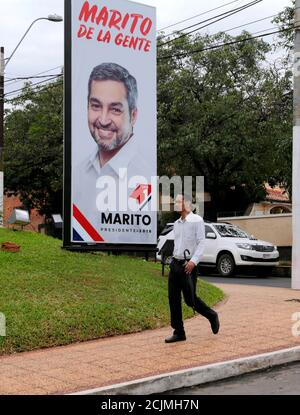 A man walks in front of a banner, displaying Paraguay's presidential candidate Mario Abdo Benitez, of the Colorado Party in Asuncion, Paraguay March 21, 2018. REUTERS/Jorge Adorno