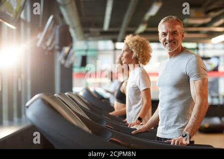 Portrait of mature man smiling at camera during his training on treadmill with other people training in the background