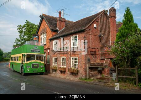 The Sloop Inn pub with an old green double-decker bus parked outside near Scaynes Hill, East Sussex, UK - Stock Photo