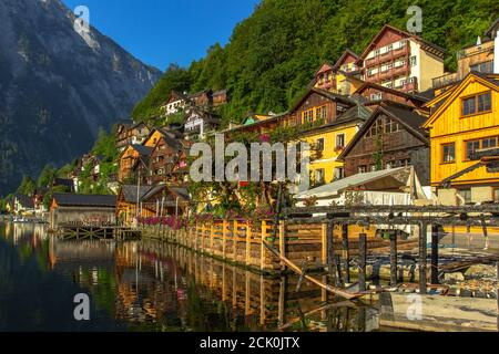 Classic postcard view of famous Hallstatt lakeside town, Austria. Scenic panoramic view of beautiful town reflecting in Hallstatter See.Beautiful sunn