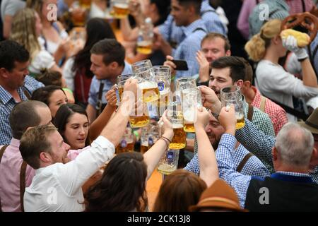 Visitors cheer with beers in a tent during Oktoberfest in Munich, Germany, September 22, 2019. REUTERS/Andreas Gebert