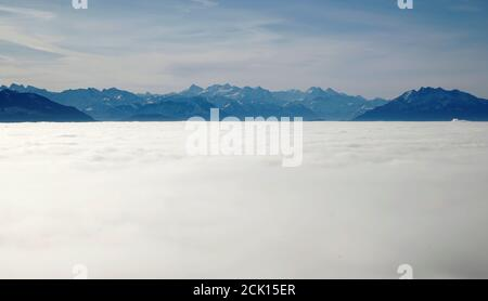 The Alps of Bernese Oberland and Mount Pilatus are seen behind the fog covered landscape from a lookout near Albispass mountain pass, Switzerland December 5, 2019. REUTERS/Arnd Wiegmann - Stock Photo