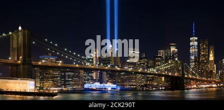 9/11 Tribute in Light. Brooklyn Bridge and Lower Manhattan illuminated at night. View from Main Street Park. - Stock Photo