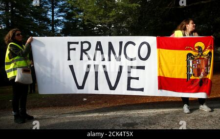 General Franco's supporters hold a banner and a Spanish Franco era flag outside The Valle de los Caidos (The Valley of the Fallen) in San Lorenzo de El Escorial, Spain, October 24, 2019. REUTERS/Javier Barbancho - Stock Photo
