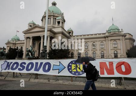 A man walks past a banner in front of Serbian parliament building in central Belgrade, Serbia, March 27, 2018. REUTERS/Marko Djurica