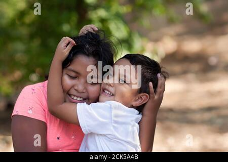 Little brother is hugging his older sister with his arms around her face and both are smiling in outdoor setting.