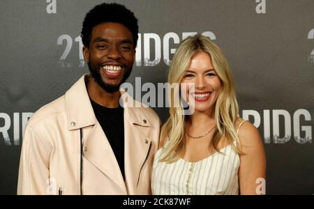 Cast members Chadwick Boseman and Sienna Miller pose at a photo call for the movie '21 Bridges' in Los Angeles, California, U.S., November 9, 2019. REUTERS/Mario Anzuoni