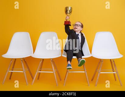 Little child is winner. Kid on the background of bright yellow wall. Smart power concept. The Cup for first place. Stock Photo