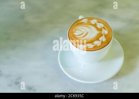 Close-up of a cup of latte is on the marble table, a white ceramic cup of coffee latte with latte art. Flat lay. Top view. - Stock Photo