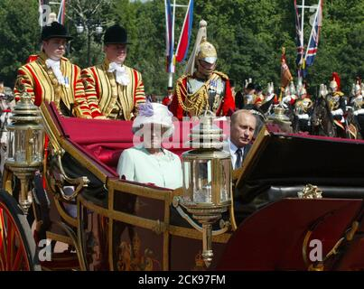 A carriage carrying Britain's Queen Elizabeth II and Russian President Vladimir Putin is escorted by royal guards to Buckingham Palace in central London June 24, 2003. Putin is on the first state visit by a Russian leader since 1844, when Nicholas I visited the British Isles at the invitation of Queen Victoria. REUTERS/Grigory Dukor  gd