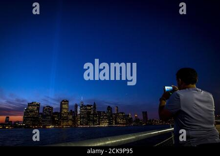 A man photographs the Tribute in Light illuminated over lower Manhattan during events marking the 13th anniversary of the 9/11 attacks on the World Trade Center, in Brooklyn, New York September 11, 2014. This year, for perhaps the first time since the attacks, a sense of normalcy and openness has taken root in the city blocks where two airliners hijacked by militants from al Qaeda crashed into the World Trade Center's twin towers. REUTERS/Brendan McDermid (UNITED STATES- Tags ANNIVERSARY - Tags: TPX IMAGES OF THE DAY DISASTER SOCIETY ANNIVERSARY POLITICS) - Stock Photo