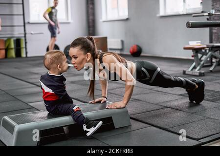 Young fit woman doing push-ups and kissing her little son