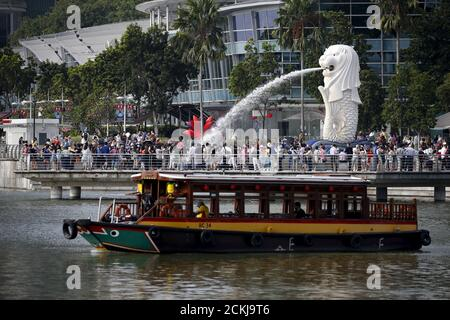 A bumboat passes tourists at the Merlion Park in Singapore, February 22, 2016. Singapore will release the fourth quarter GDP on Wednesday. REUTERS/Edgar Su