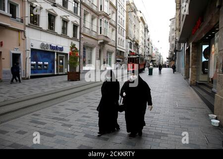 Women wearing protective face masks and gloves are seen as the spread of the coronavirus disease (COVID-19) continues, Istanbul, Turkey, March 26, 2020. REUTERS/Umit Bektas - Stock Photo