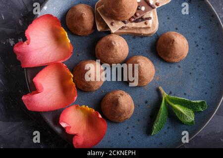 Chocolate truffle on blue ceramic plate on black concrete background decorated with rose petals. close up, top view