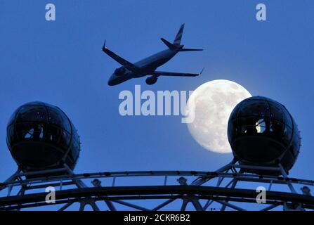 A British Airways passenger jet flies past the full moon as passengers travel on the London Eye February 16, 2011. REUTERS/Toby Melville (BRITAIN - Tags: TRANSPORT CITYSCAPE ENVIRONMENT SOCIETY IMAGES OF THE DAY TRAVEL) - Stock Photo