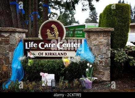 Flowers are seen near the sign outside Life Care Center of Kirkland, a long-term care facility linked to several confirmed coronavirus cases, in Kirkland, Washington, U.S. March 13, 2020.  REUTERS/Lindsey Wasson - Stock Photo