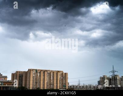 gurgaon delhi cityscape with monsoon clouds casting shadows on high rise apartments and buildings showing passage of time and rapid growth of real